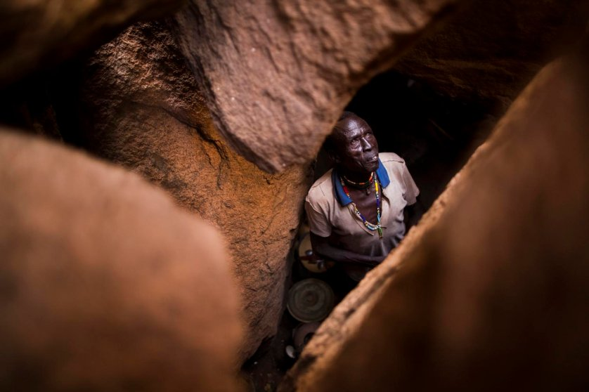 An older Nuban man looks up from his home in a cave after hiding for months from bombings by the SAF.