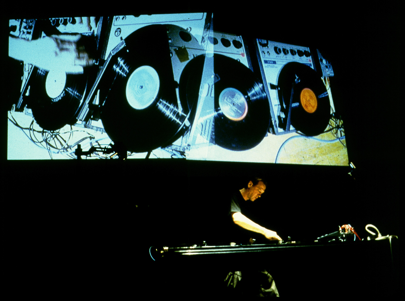 Christian Marclay performing, 1999, Festival Agora, IRCAM, Paris.                                                              A pioneer of the turntablist movement, Marclay's performative work has involved active mixing of sound through the use of turntables. His live performance transcends the latitude of just an auditory experience—as they frequently involve unconventional means of creating sound, such wearing the turntable on his body.