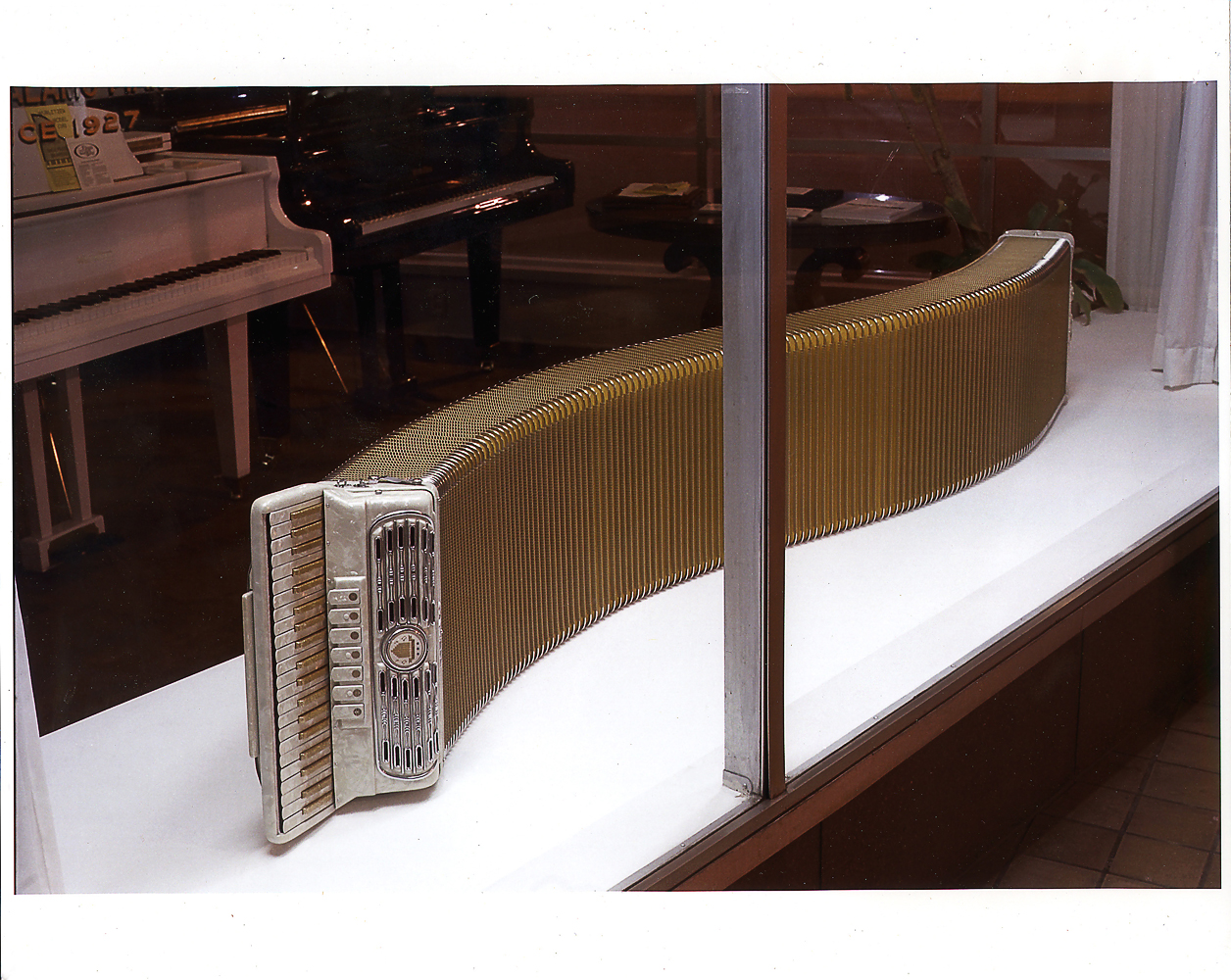 Accordion, 1999                                                              Connecting sound to visual experience is focal in Marclay's practice— Accordion, pictured here, is a sculpture comprising an altered piano accordion stretched to an almost hyperbolic length, reflecting the winding, breathy nature of the instrument's sound.