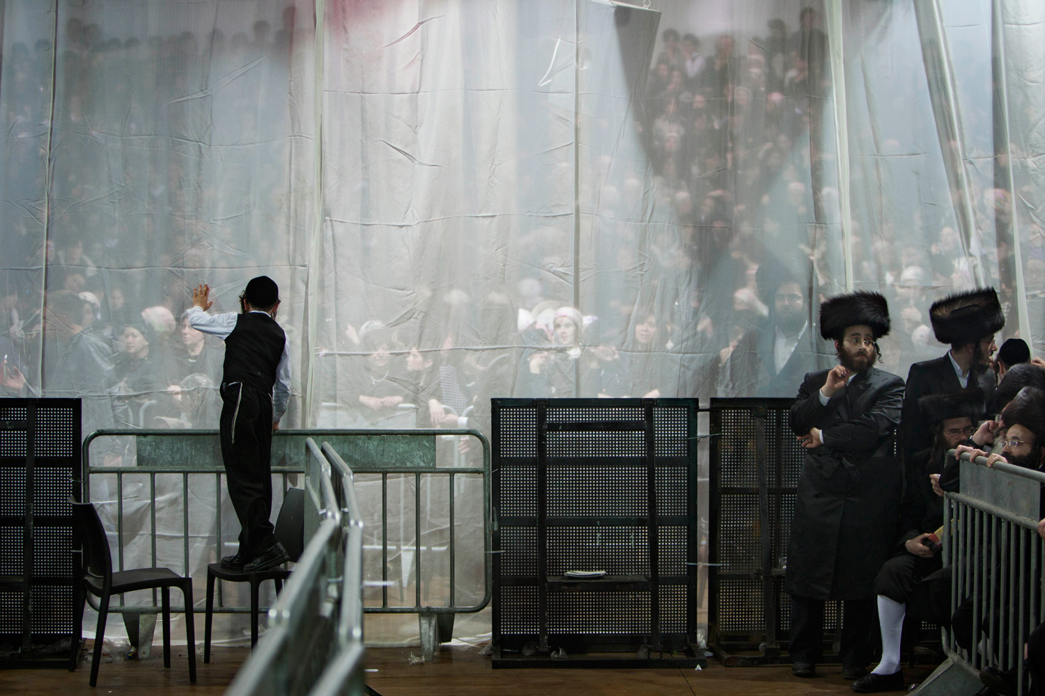 Feb. 14, 2012. Ultra-Orthodox Jews gather for the traditional Jewish wedding for Chananya Yom Tov Lipa, the great-grandson of the Rabbi of the Wiznitz Hasidic followers, in the Israeli town of Petah Tikva near Tel Aviv. The gauze curtain is used to separate men and women during the wedding.