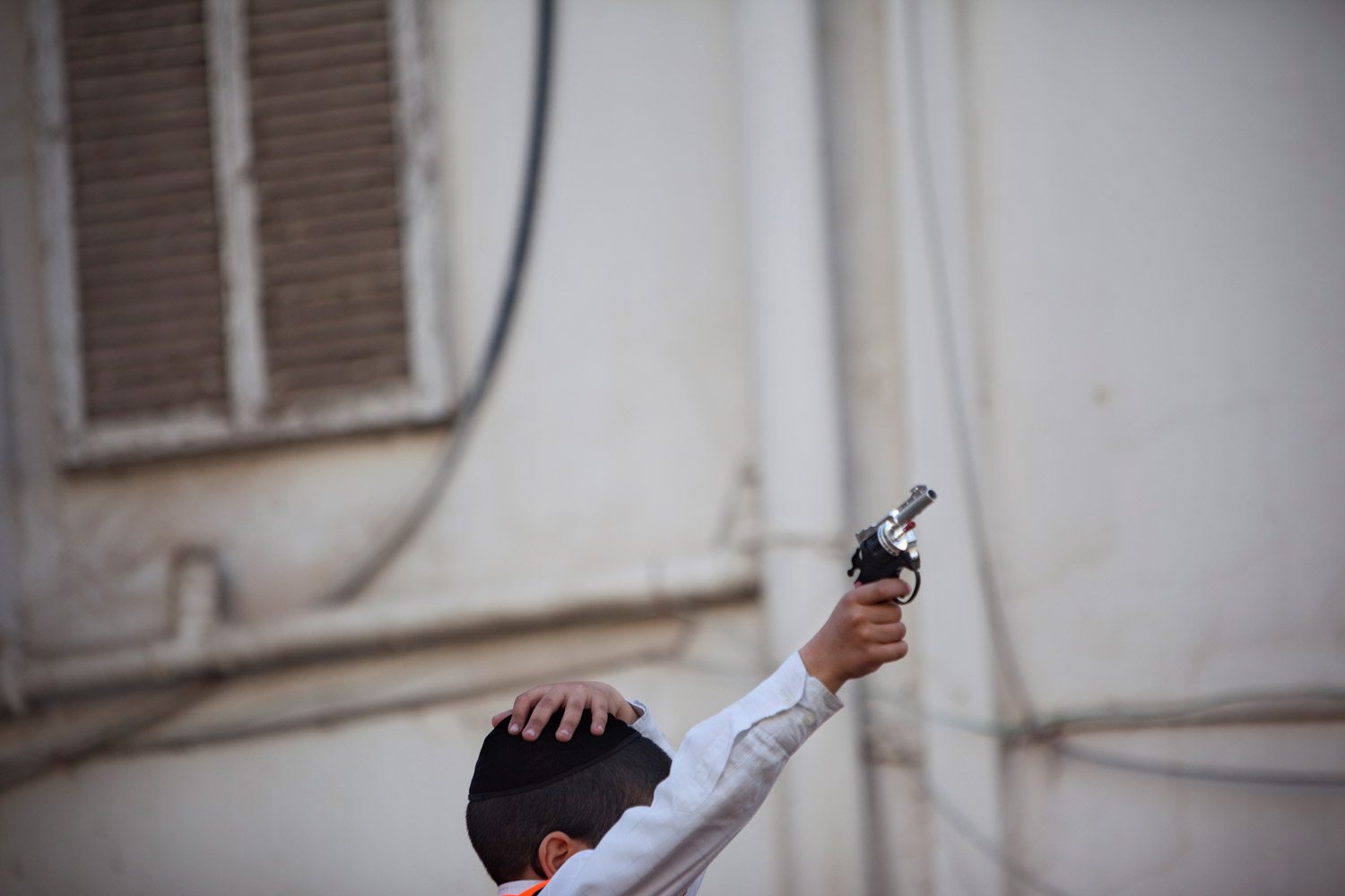 March 8, 2012. An ultra-Orthodox Jewish boy plays with a toy gun during a Purim festival in the ultra-Orthodox town of Bnei Brak near Tel Aviv.