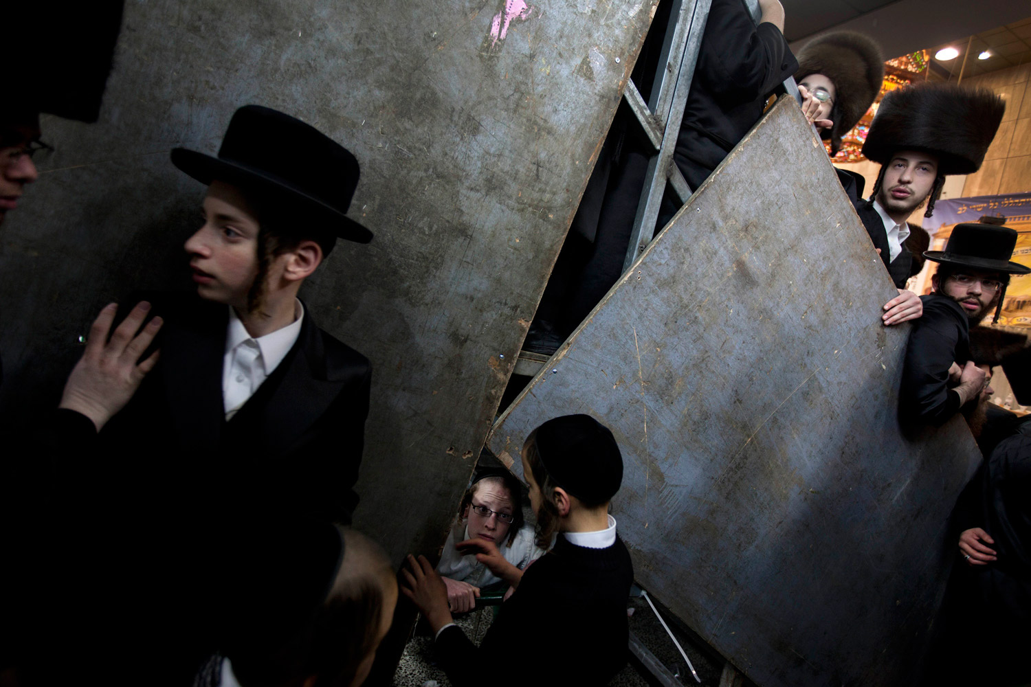 Feb. 16, 2012. Ultra-Orthodox Jewish men crowd together to watch the Sheva Brachot ceremony two days after the traditional Jewish wedding for Chananya Yom Tov Lipa, the great-grandson of the Rabbi of the Wiznitz Hasidic followers, in the ultra-Orthodox town of Bnei Brak near Tel Aviv. The Sheva Brachot in Hebrew, or the seven blessings in English, is a special Jewish wedding blessing.