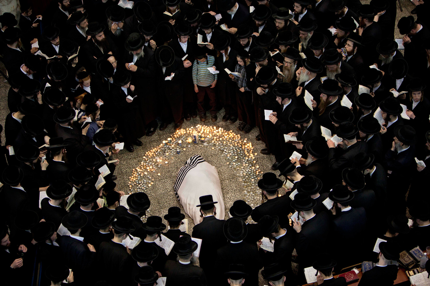March 14, 2012. Ultra-Orthodox Jews gather around the body of Rabbi Moshe Yehoshua Hager, leader of the~Hassidic sect Vizhnitz in Israel, at the Vizhnitz Synagogue during his funeral procession in Bnei Brak, Israel.