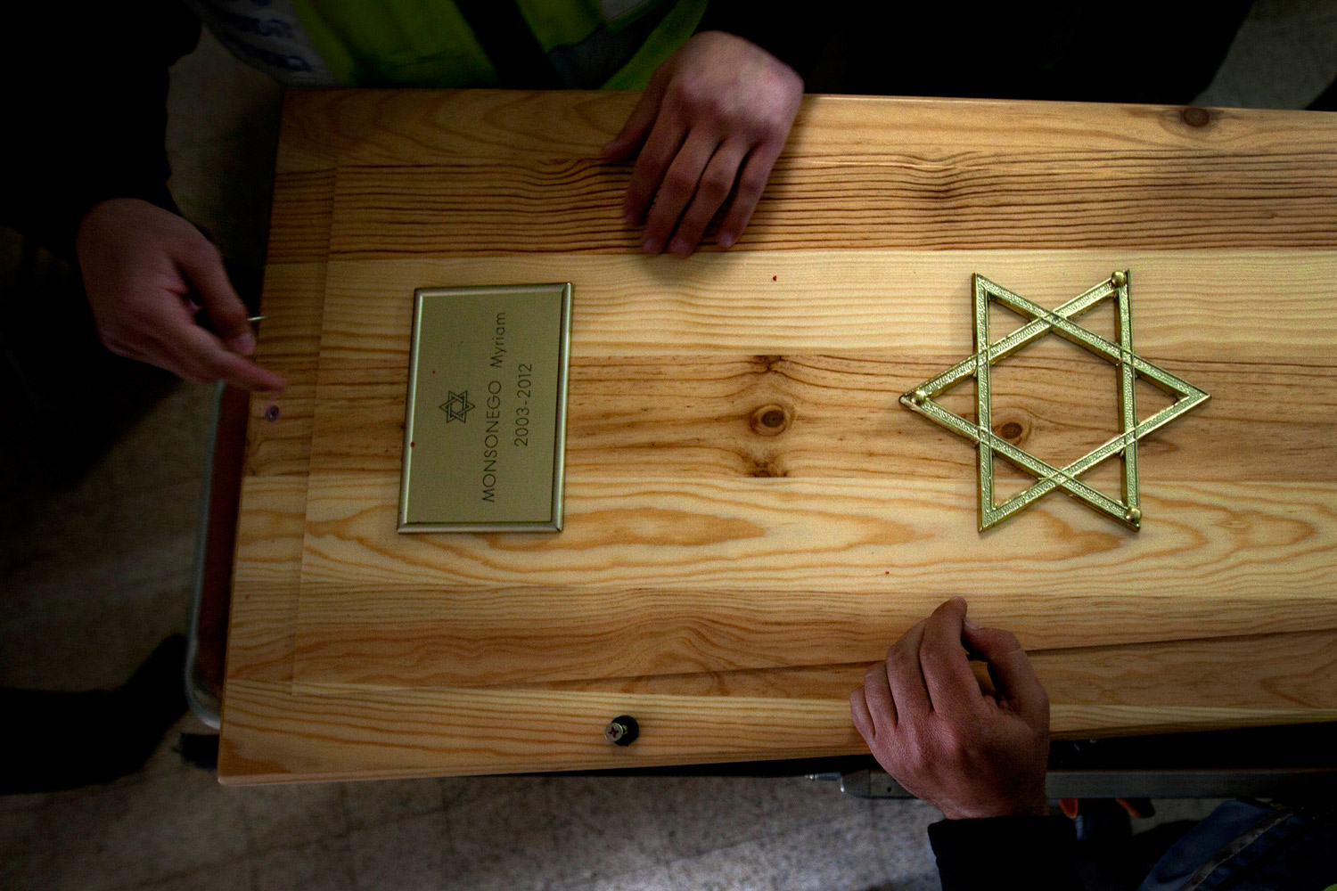 March 21, 2012. Members of ZAKA rescue and recovery open the coffins of Toulouse shooting victims as they prepare the bodies for burial after they arrived at a morgue in Jerusalem. The three children and a rabbi were gunned down the deadliest school shooting France has ever known and the bloodiest attack on Jewish targets in decades.