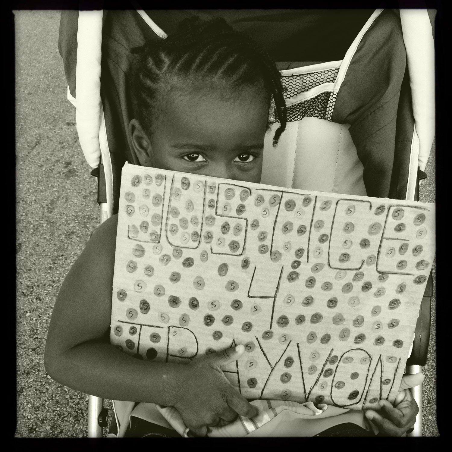 A little girl holds a handmade justice for Trayvon Martin poster at the annual Dr. Martin Luther King Jr. candlelight memorial service, Miami, FL, April 4, 2012