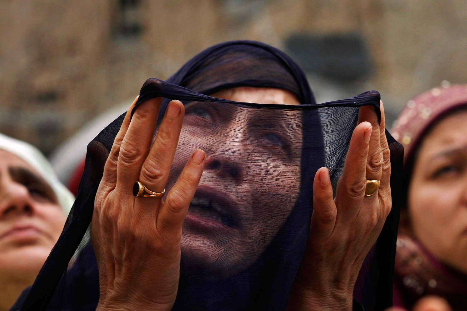 May 14, 2012. A Kashmiri Muslim woman prays as a head priest, unseen, displays a relic, believed to be a hair from the beard of the Prophet Mohammad, during special prayers on the death anniversary of Abu Bakr Siddiq, the first Caliph of Islam, at Hazratbal Shrine on the outskirts of Srinagar, India.