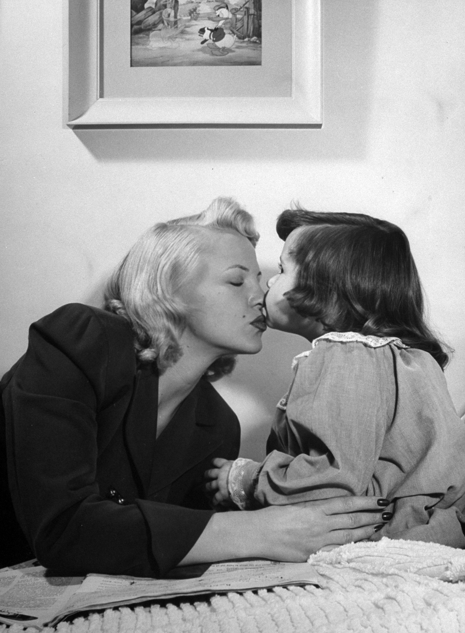 Peggy Lee gets a goodnight kiss from her 4-year-old daughter Nicki, 1948.