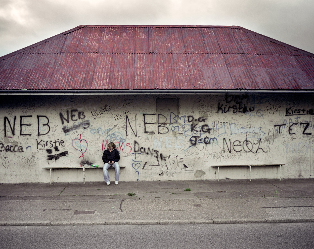 A teenage girl waits for her friends on the streets of Elgin. With a population of 21,000 and it's situation on a main arterial road, Elgin is big enough to experience some of the social issues associated with larger urban areas, while still being situated in predominantly rural region. 2007.