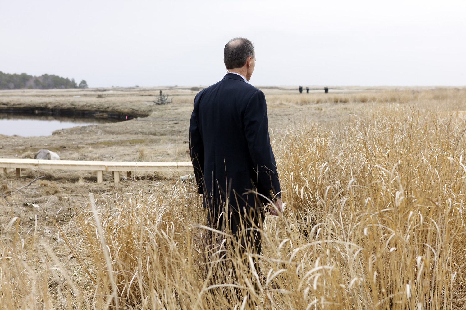 April 22, 2004. A Secret Service agent stands guard during President George W. Bush's visit to the Wells National Estuarine Research Reserve in Wells, Maine.