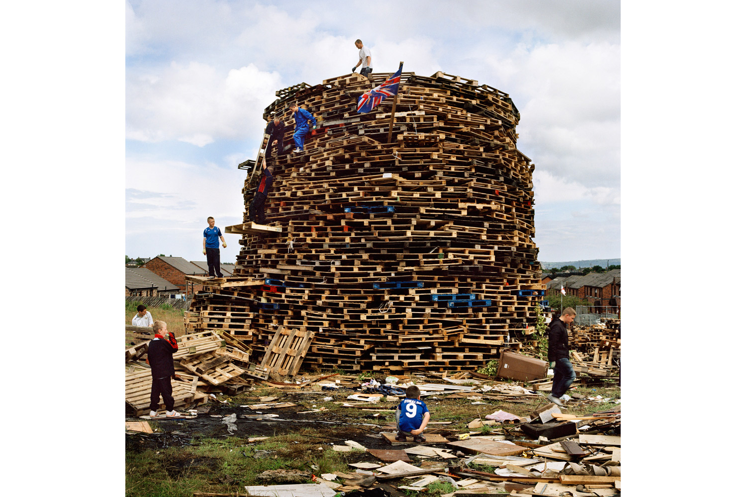Each year, youth in loyalist Upper Ardoyne build a bonfire to be set alight on the evening of July 11 as part of the annual celebrations held to commemorate the victory of Protestant King William of Orange over the Catholic King James II, in 1690. Young people in Protestant estates such as this spend weeks scavenging wood to build the structure, and even stand watch, fearing that it may be attacked and destroyed by rival Catholic youth. 2011.