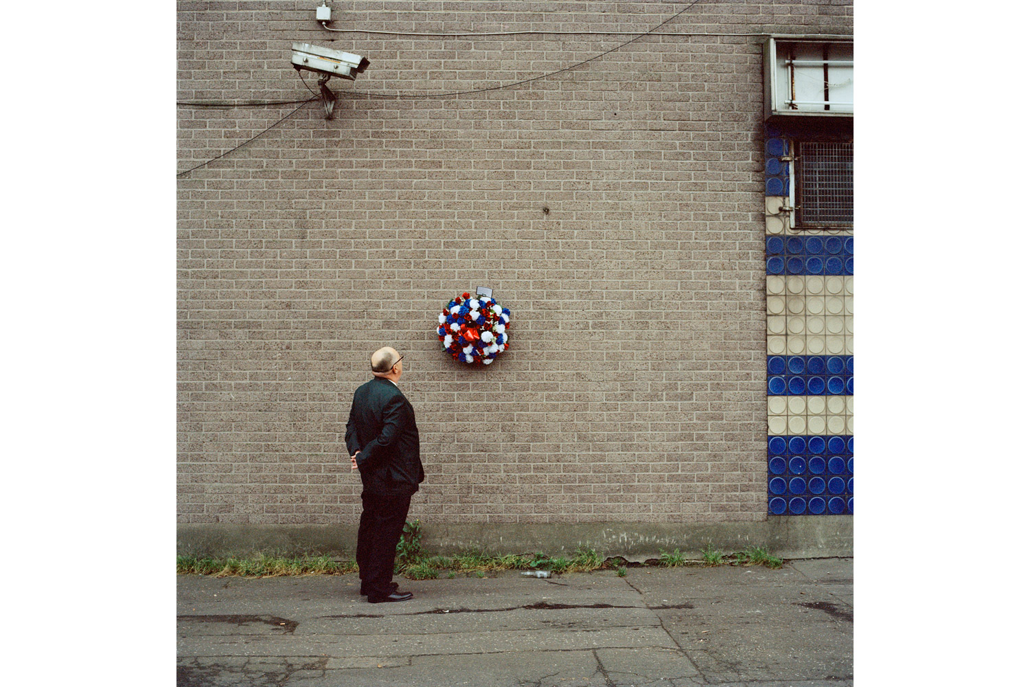 Tommy looks on at a remembrance wreath for two murdered UDA members, both killed by the UVF (Ulster Volunteer Force) during a loyalist feud. 2011.
