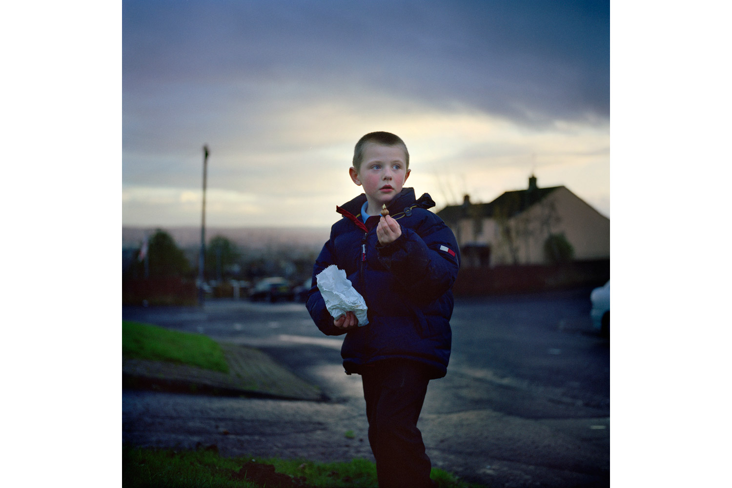 A young boy in Ballysillan estate plants flower bulbs as part of the final Re-Imaging Communities Project effort in the area. In Ballysillan, many locals feared that the removal of traditional murals meant having their culture and memories stripped away. After careful delegation, new sculptures, murals and gardens have been designed and installed by residents.