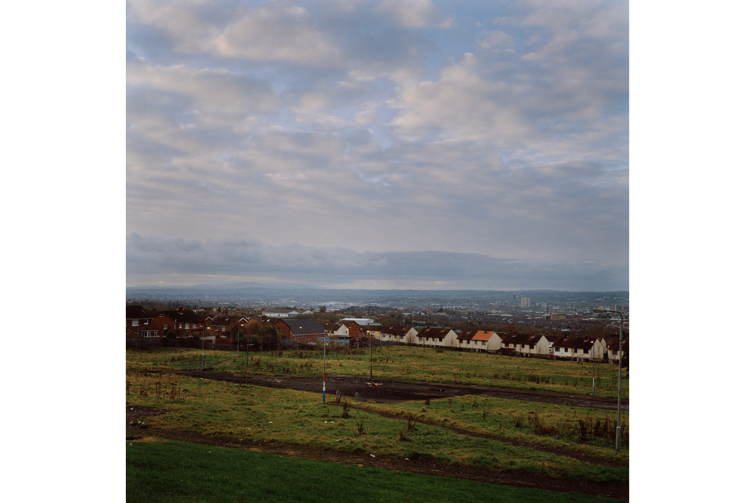 Looking down from North Belfast over the city proper. Flag poles are painted in red, white and blue — the colors of the British Union Jack — as a traditional method of marking territory in Protestant estates. 2010.