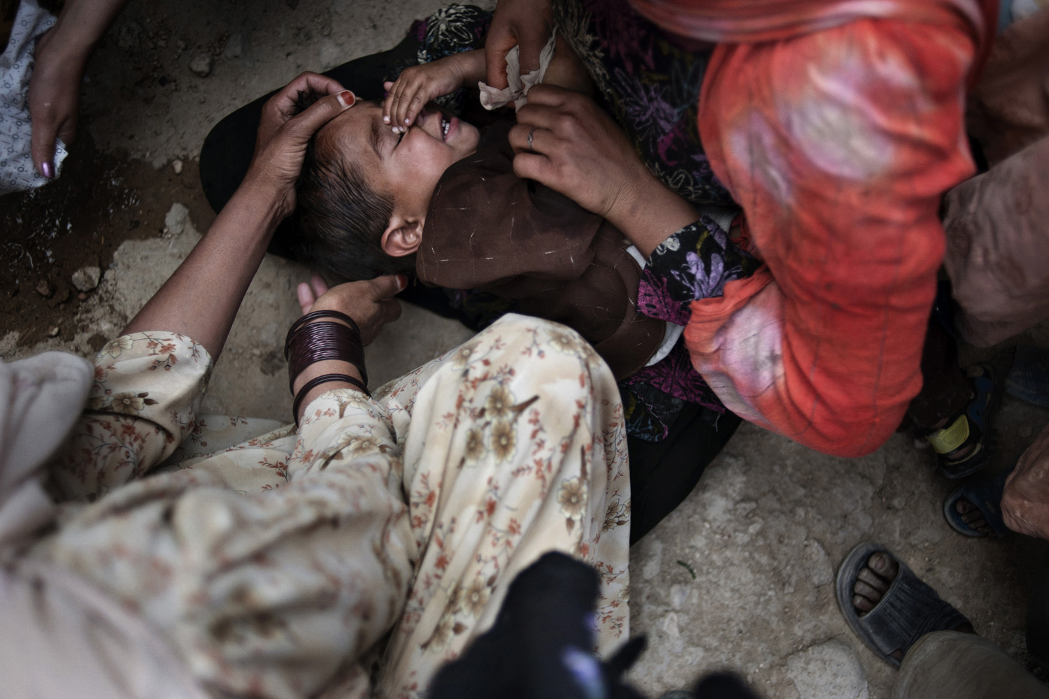 Widows care for a child who sliced his head while playing on old Soviet military remnants in Kabul, Afghanistan, July 9, 2011.