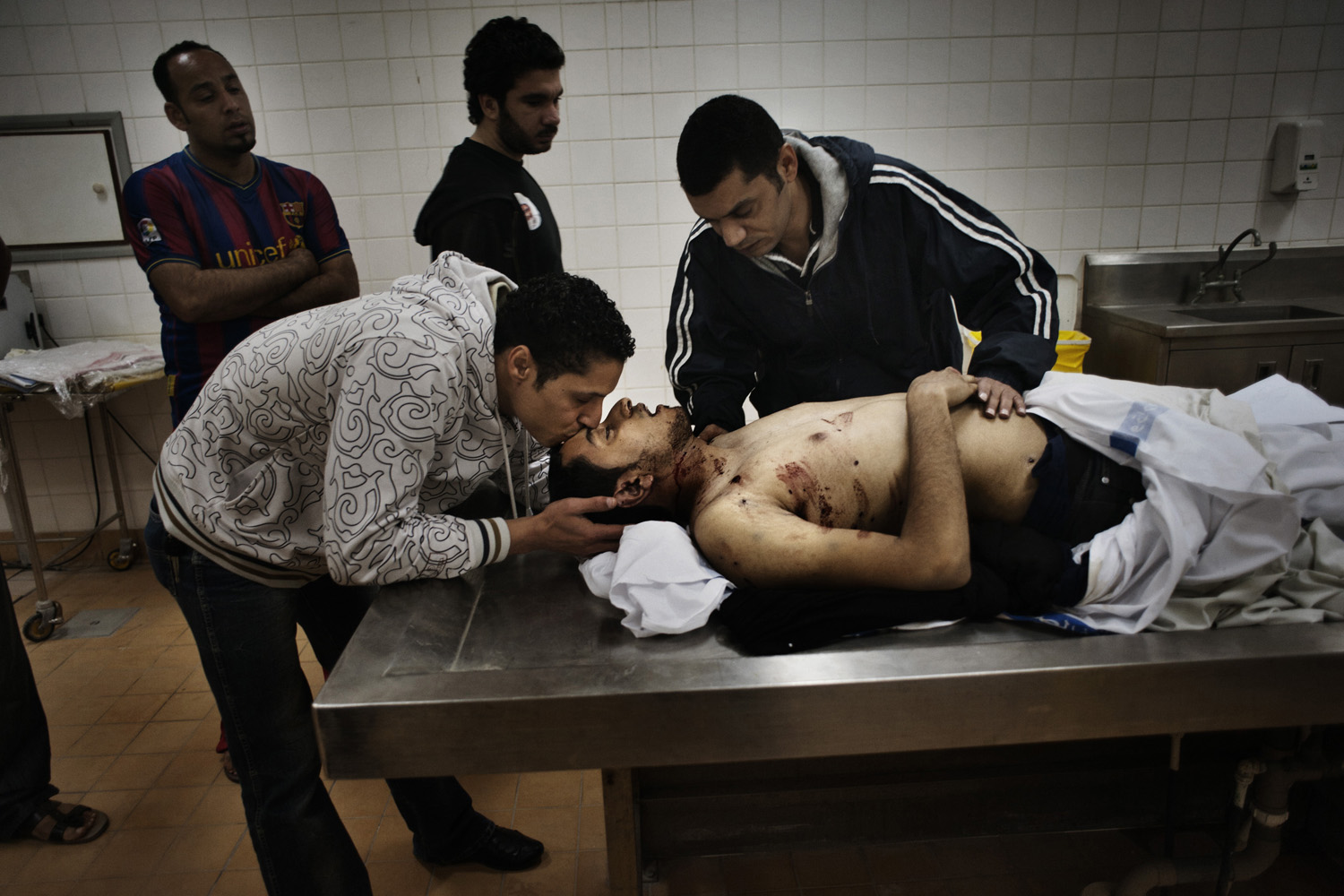 A man kisses his brother in the morgue of Bahrain's Central hospital. The man was shot with a pellet gun by Bahraini police in February, 2011.