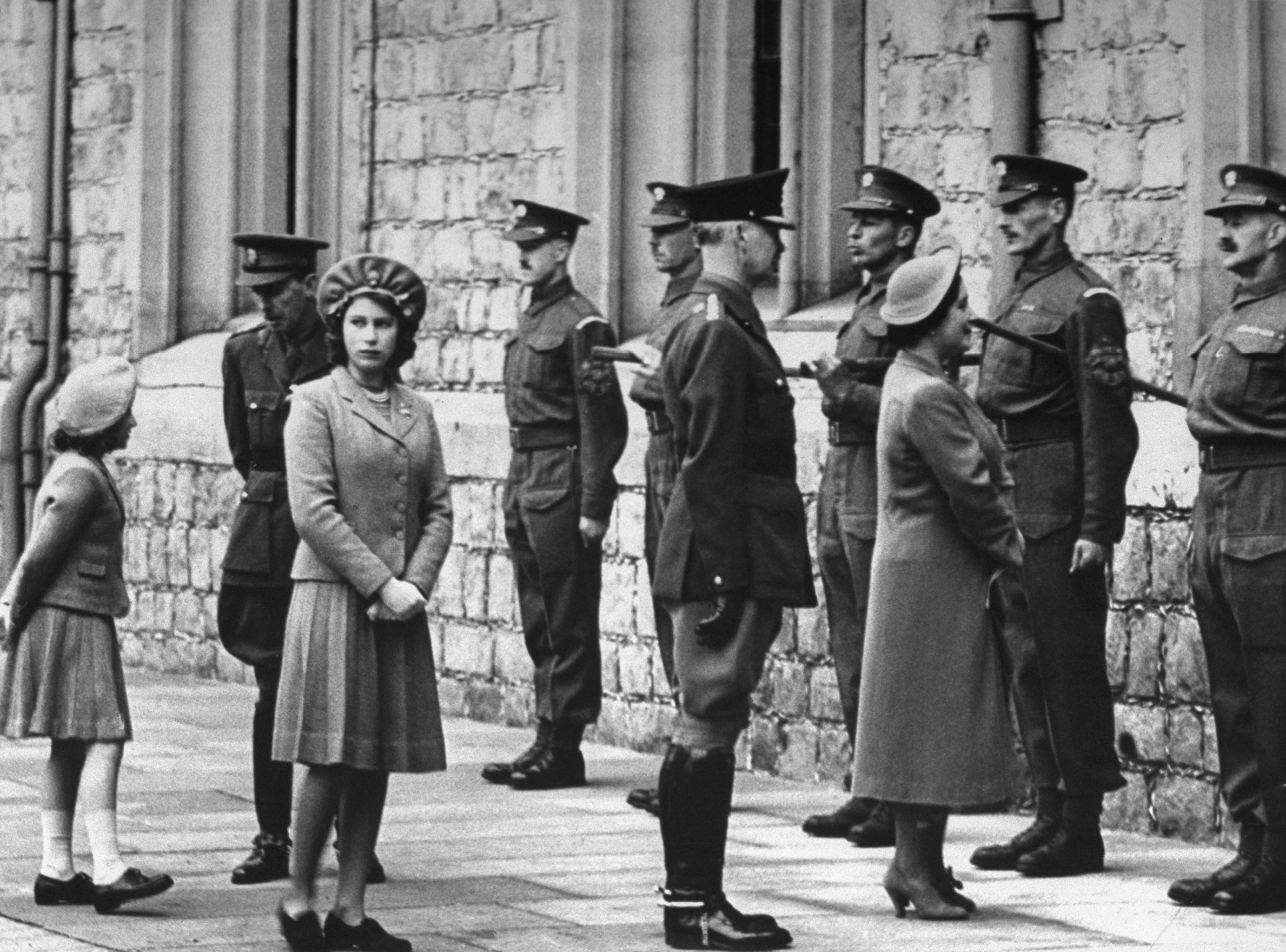 Princess Margaret (left), the future Queen Elizabeth II (third from left) and the Queen Mother (third from right) with the Grenadier guards on the occasion of Princess Elizabeth's birthday, 1942.