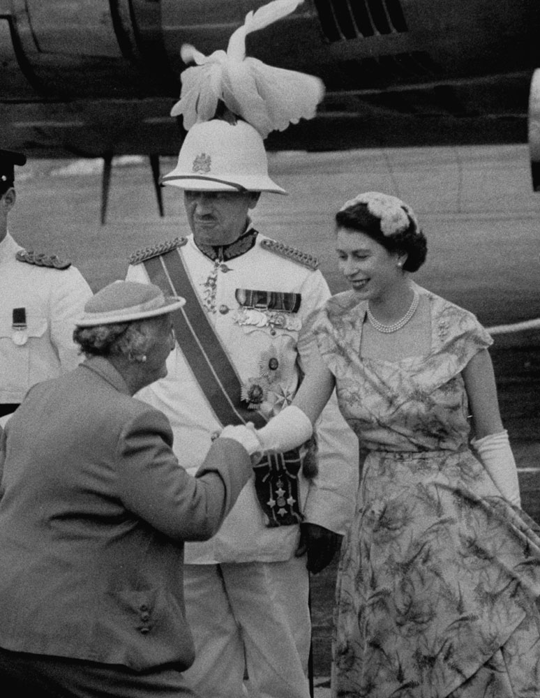 Queen Elizabeth II shakes hands with a well-wisher while standing next to the General and Governor of Bermuda, Sir Alexander Hood, 1961.