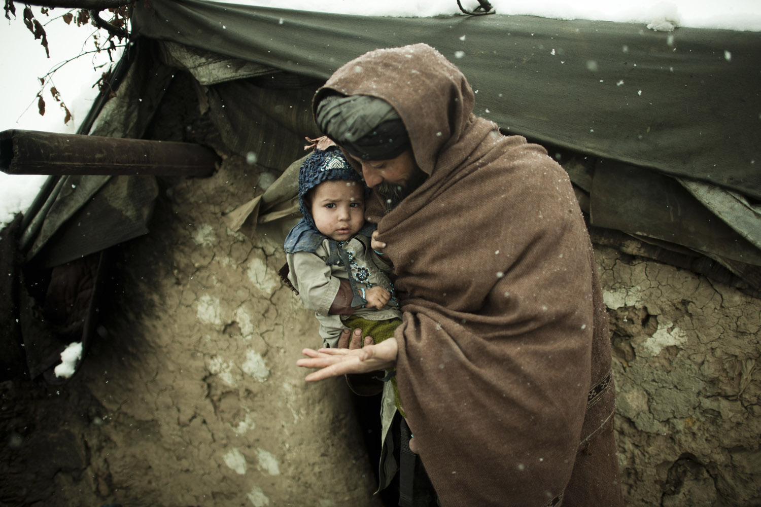 Ibrahim holds his youngest son outside a mud hut where he lives with his wife and 11 children. The same camp buried at least two children who died due to the freezing temperatures in late January, 2012.
