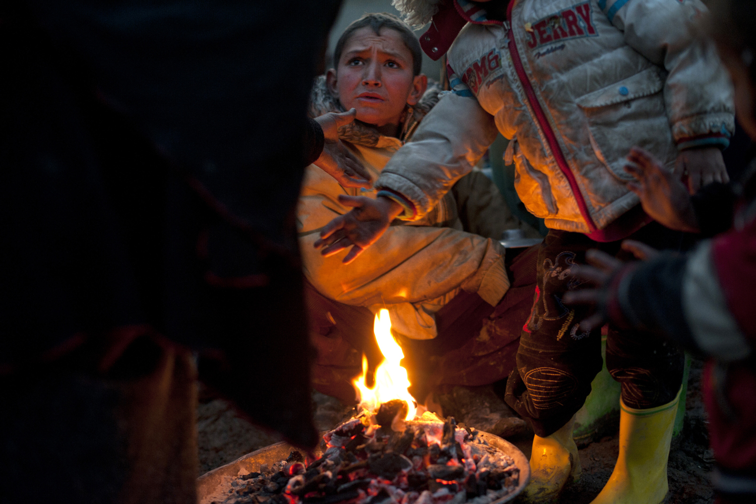 A boy fights over a fire in one of 45 refugee camps in Kabul. Eight children reportedly froze to death in camps like this one in Kabul in the below-freezing temperatures in late January, 2012.