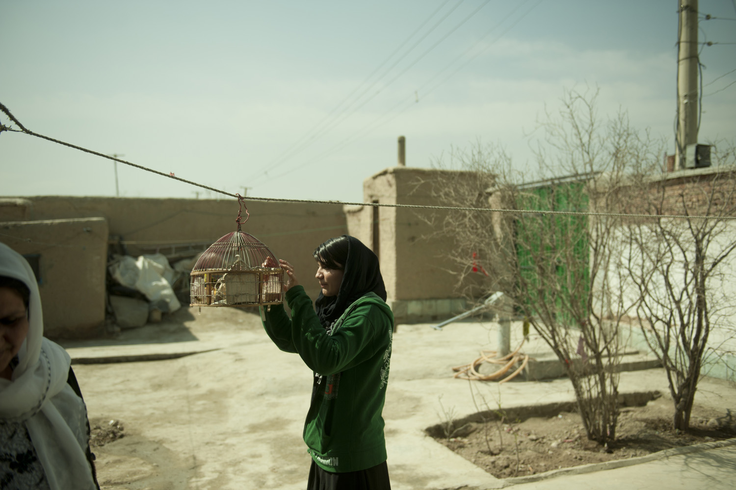 Rahimi visits her family's pet bird in her Kabul home