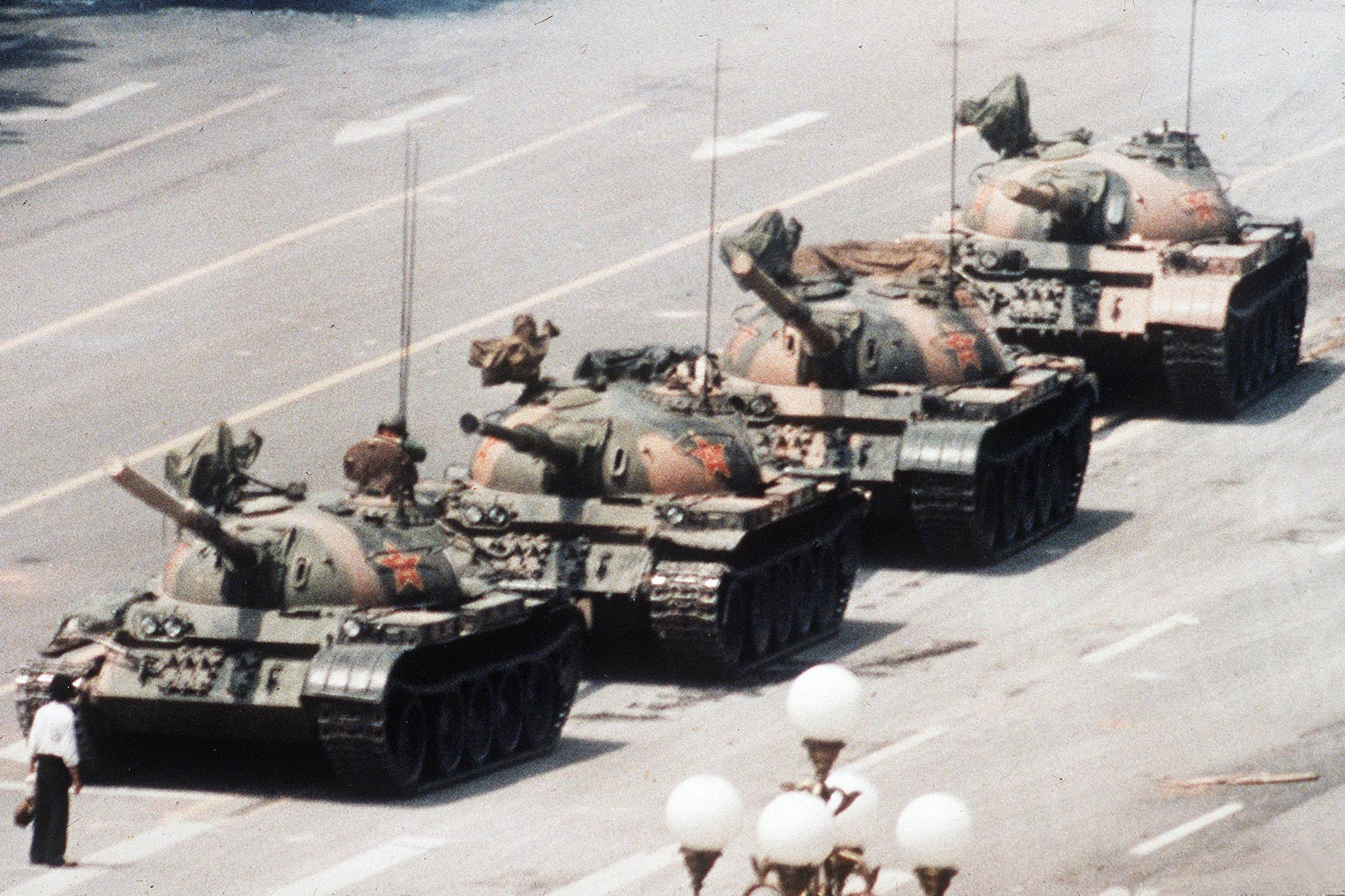 A Chinese man stands alone to block a line of tanks heading east on Beijing's Changan Avenue in Tiananmen Square on June 5, 1989. The man, calling for an end to the recent violence and bloodshed against pro-democracy demonstrators, was pulled away by bystanders, and the tanks continued on their way.