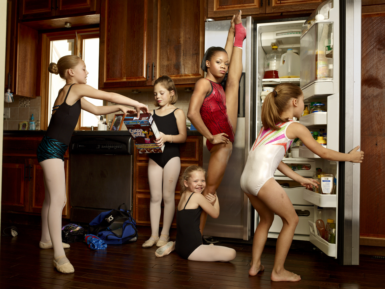 Douglas, who is from Virginia, lives with a host family so she can train at Chow's Gymnastics in Des Moines, Iowa. She is seen here with her young host sisters–all dancers or gymnasts themselves.