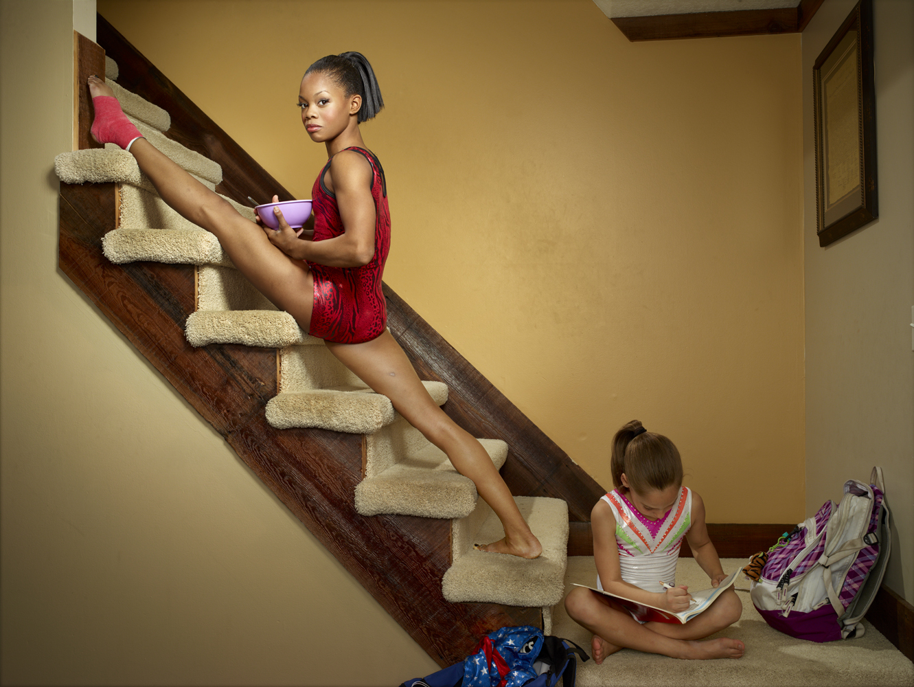Douglas eats breakfast while stretching on the stairs of her host family's home in Des Moines, Iowa.