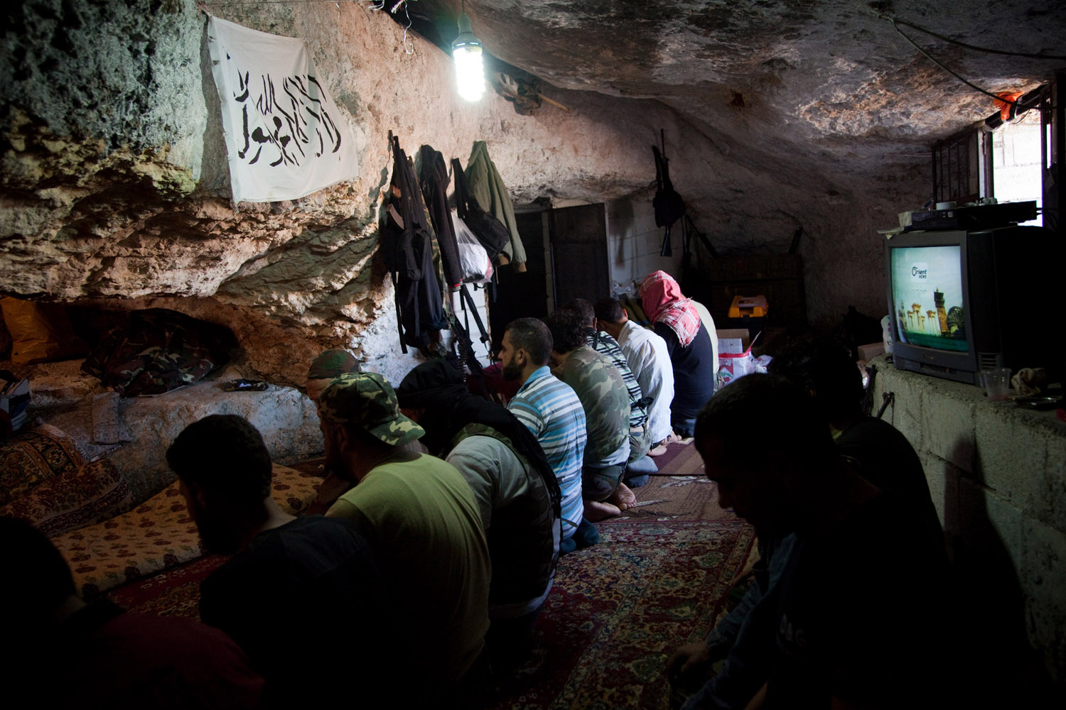 Free Syrian Army fighters pray in a cave in the mountains outside of Sarmadda, a town near the Syrian border, on June 7, 2012. The FSA are often ill-equipped to fight against the tanks, rockets and mortars used by the Syrian Army.