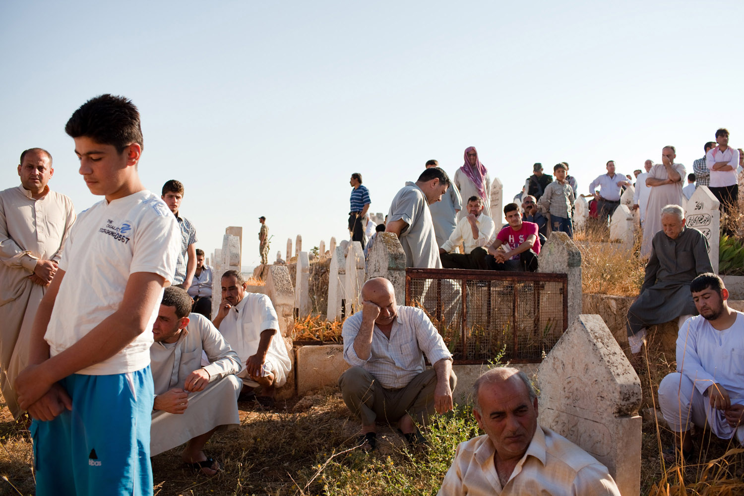 Men gather at a graveyard on the outskirts of Anadan, Syria, on June 8, 2012 to bury Fawaz Omar Abdullah, 30, a civilian who was shot and killed by a Syrian Army sniper the day before as he was walking near a checkpoint in the village.