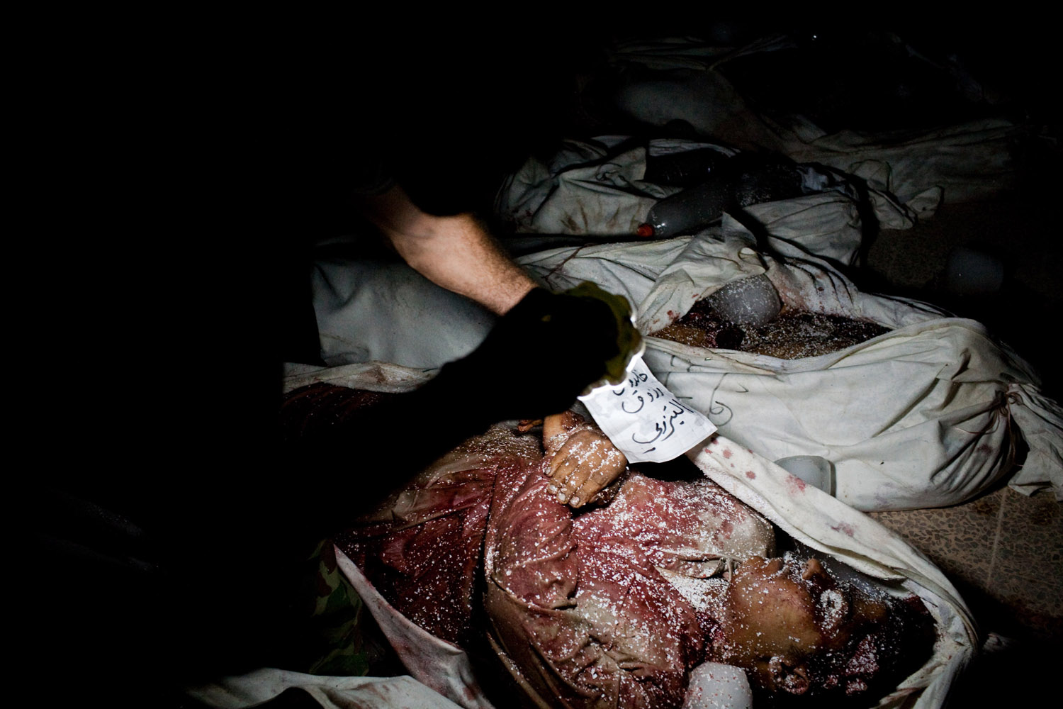 Bodies wrapped in white sheets are laid out on the ground in a mosque in Maarat Al Noman, Syria, after a day of heavy shelling by Syrian Army forces, June 9, 2012.