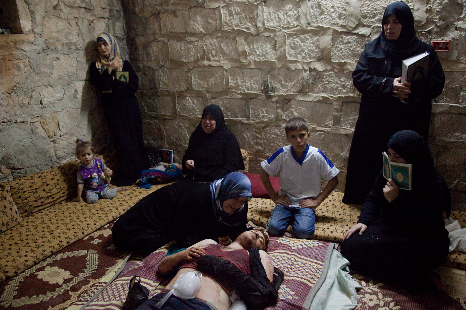 The mother of Alaa Milhem, 22, grieves over her dead son in the city of Maarat Al Noman on June 9, 2012. Alaa was a student of French Literature at the University of Aleppo and had been studying for exams when the shelling started. He was killed by a mortar shell fired by the Syrian Army while trying to help injured civilians around him.