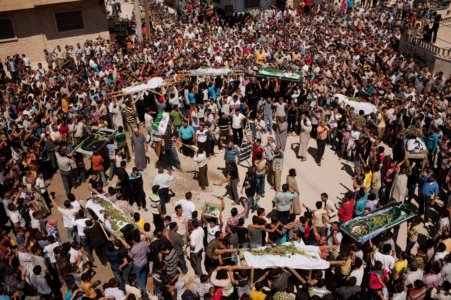 Demonstrators shout slogans as they carry the bodies of nine civilians killed the night before by mortars fired on the city of Maarat Al Noman by the Syrian Army on June 10, 2012.