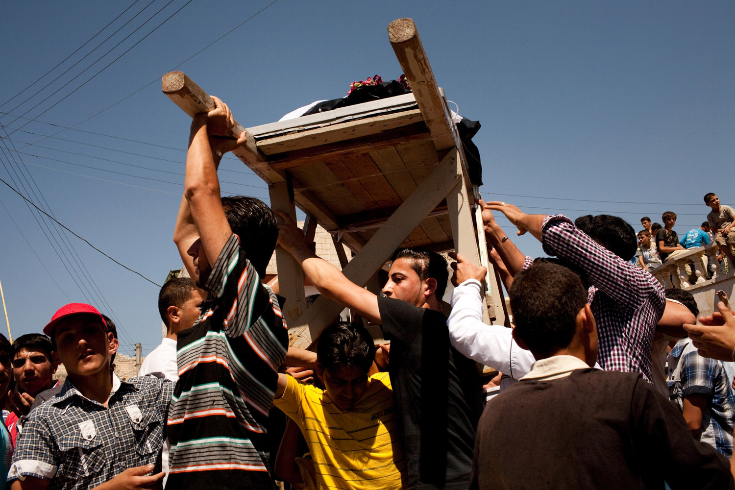 Demonstrators shout slogans as they carry the bodies of nine civilians killed the night before by mortars fired on the city of Maarat Al Noman by the Syrian Army on June 10, 2012. Estimates put the death toll between 20-30 people.