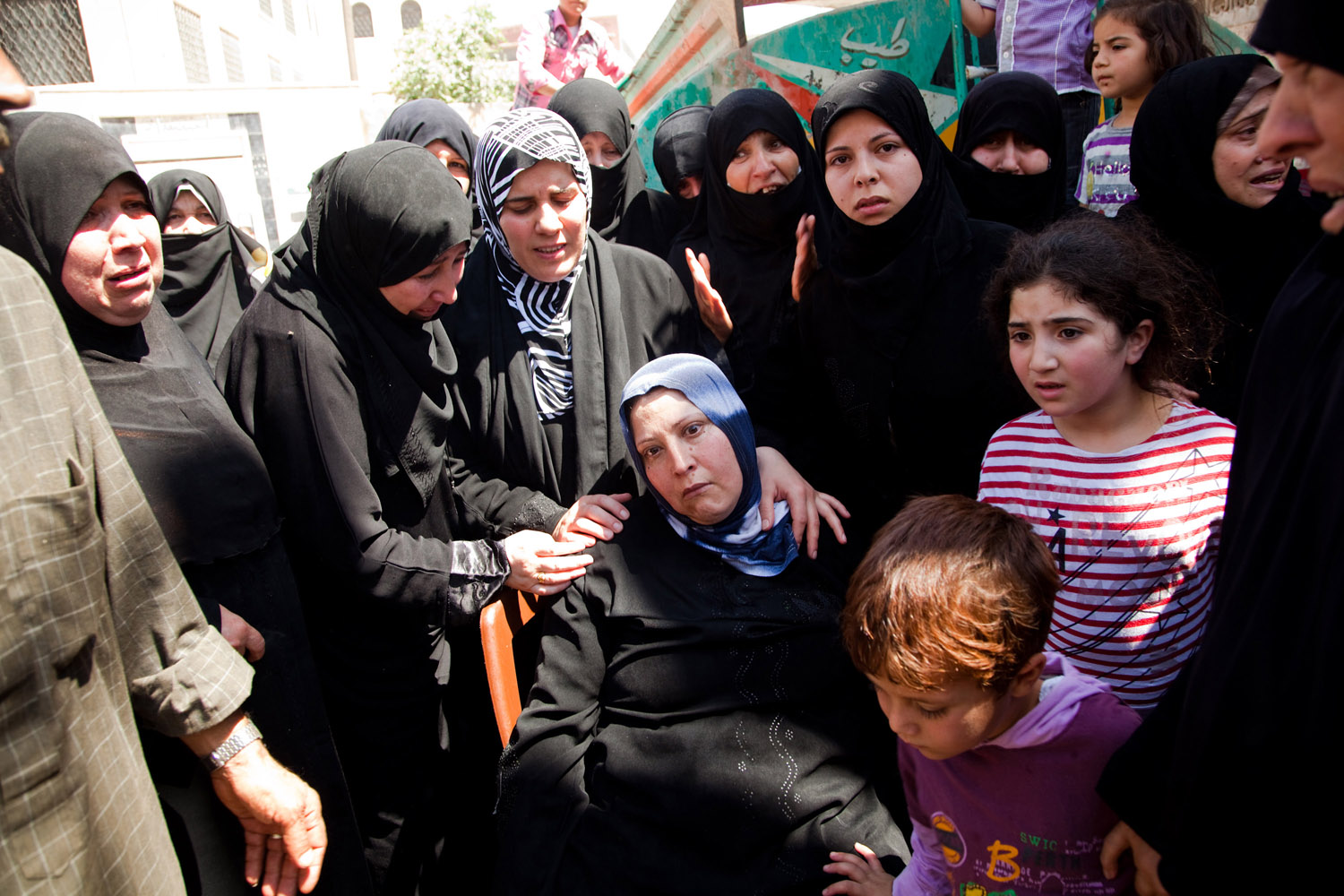 A woman faints during demonstrations that took place after many civilians were killed the night before by mortars fired on the city of Maarat Al Noman by the Syrian Army on June 10, 2012.