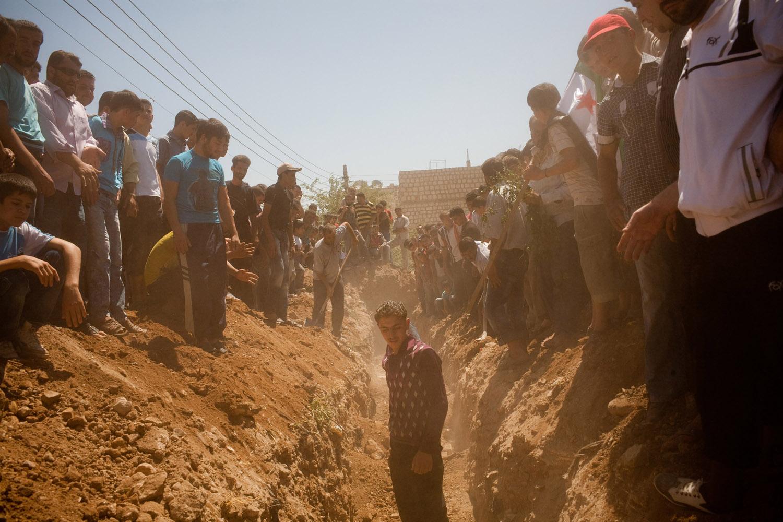 Men bury dead civilians in the Maarat Al Noman graveyard on June 10, 2012.