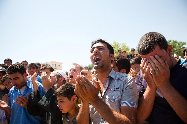 Men bury dead civilians and pray in the Maarat Al Noman graveyard on June 10, 2012.