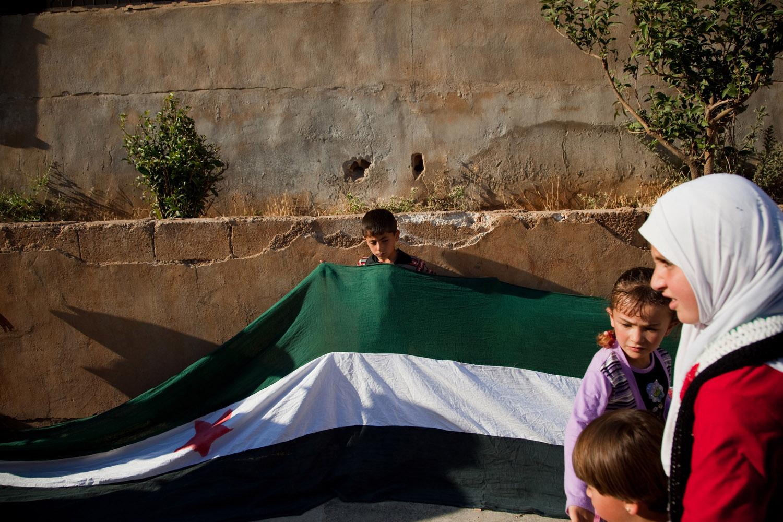 Children gather at a demonstration against Bashar al Assad's regime in a village in the Jebel al Zawiyah mountains outside of Idlib on June 10, 2012.