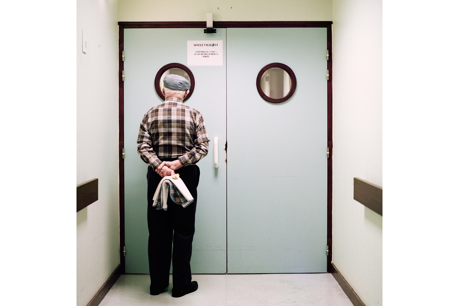 A resident stands in front of the ward's locked exit door. Passages are blocked and doors are locked to prevent residents from wandering off. Photographer Maja Daniels spent three years, beginning in 2008, documenting the ward and its residents