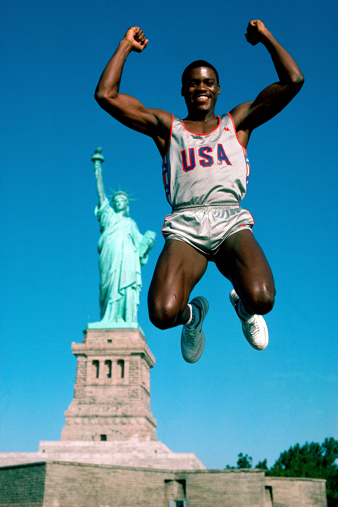 Carl Lewis jumps in front of Statue of Liberty on Liberty Island in New York Harbor, New York City.