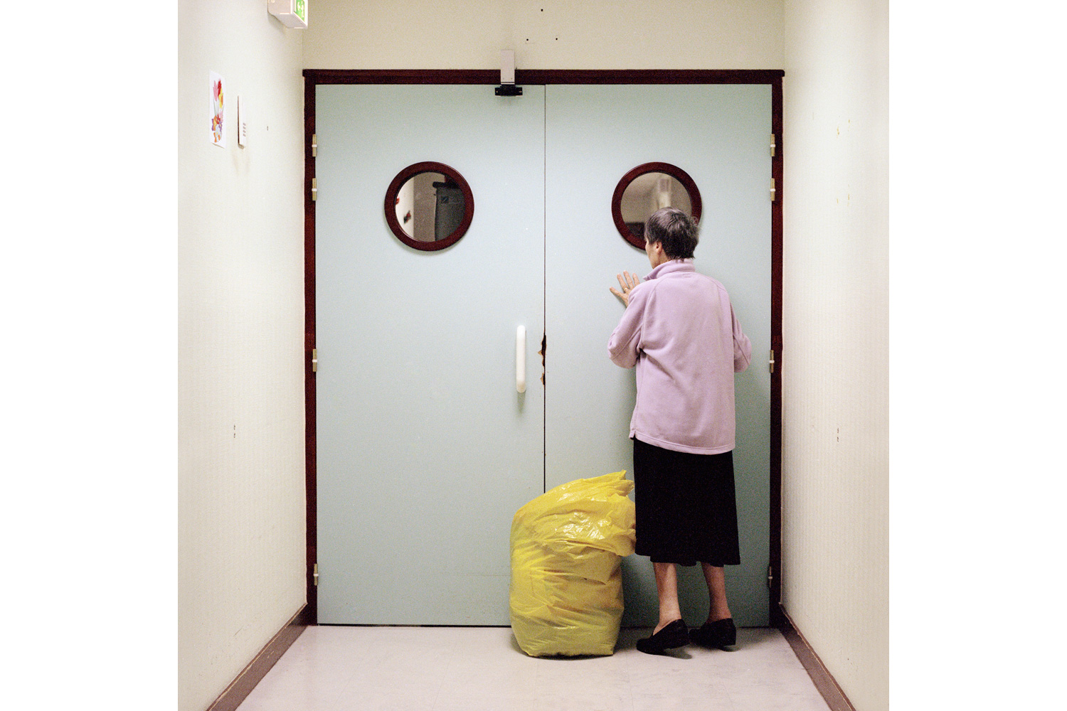 A resident stands in front of the locked ward door