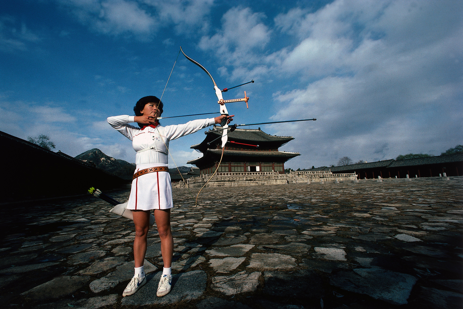 South Korean Jin-Ho Kim poses with bow and arrow in front of Gyeongbokgung Palace in Seoul.
