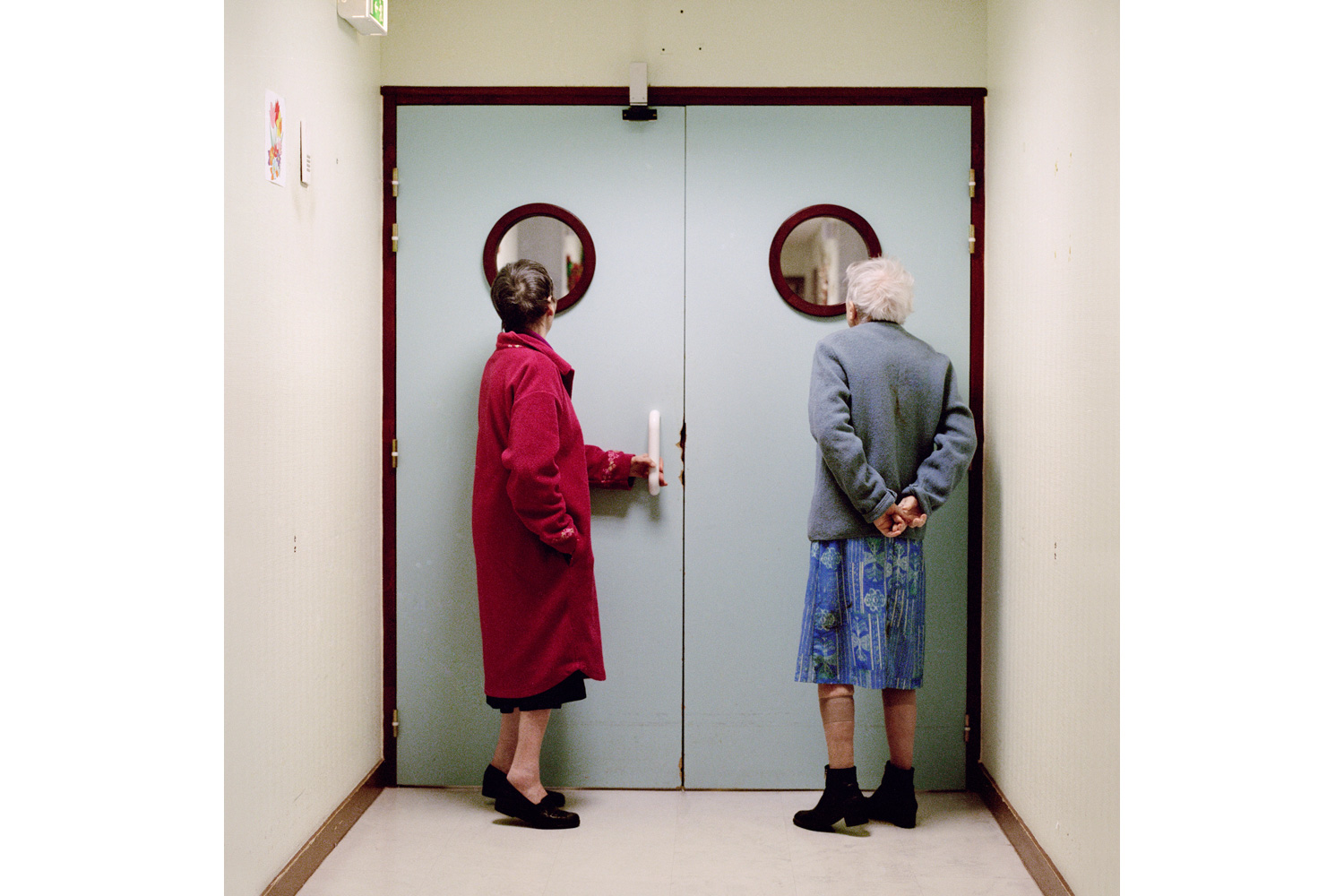 Two residents stand in front of the ward's locked exit door