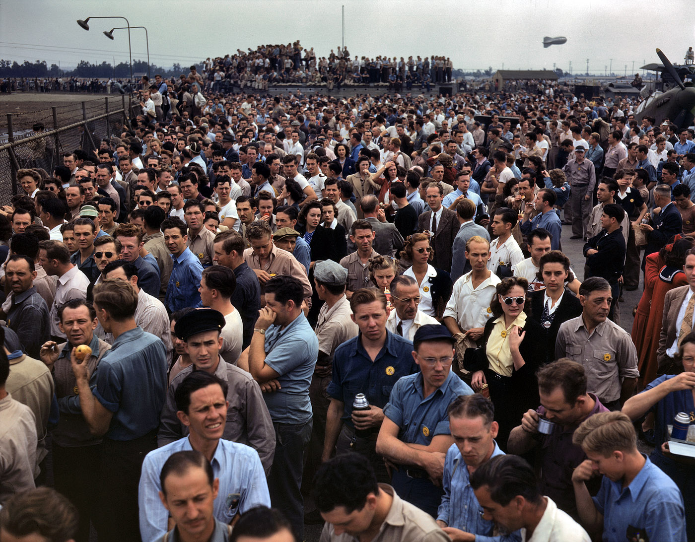 October 1942. Thousands of North American Aviation employees at Inglewood, California, look skyward as the bomber and fighter planes they helped build perform overhead during a lunch period air show. This plant produces the battle-tested B-25 'Billy Mitchell' bomber, used in General Doolittle's raid on Tokyo, and the P-51 'Mustang' fighter plane, which was first brought into prominence by the British raid on Dieppe.