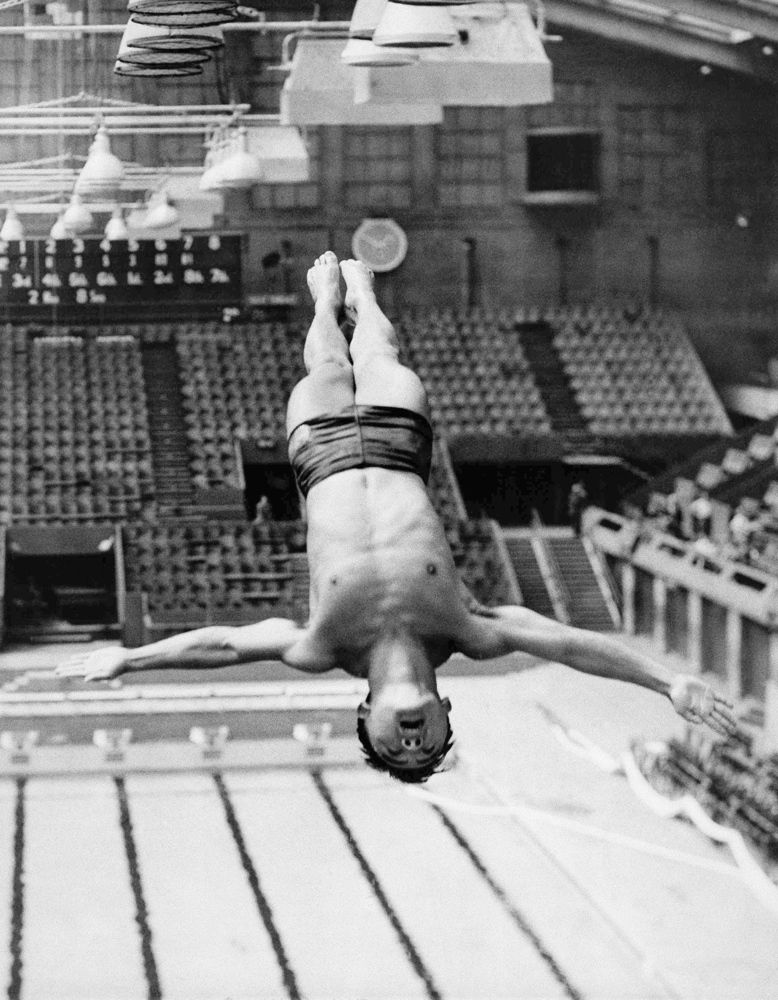 Dr. Sammy Lee glides from the top of the diving tower at the Empire Pool in Wembley, England during training for the 1948 Olympics.