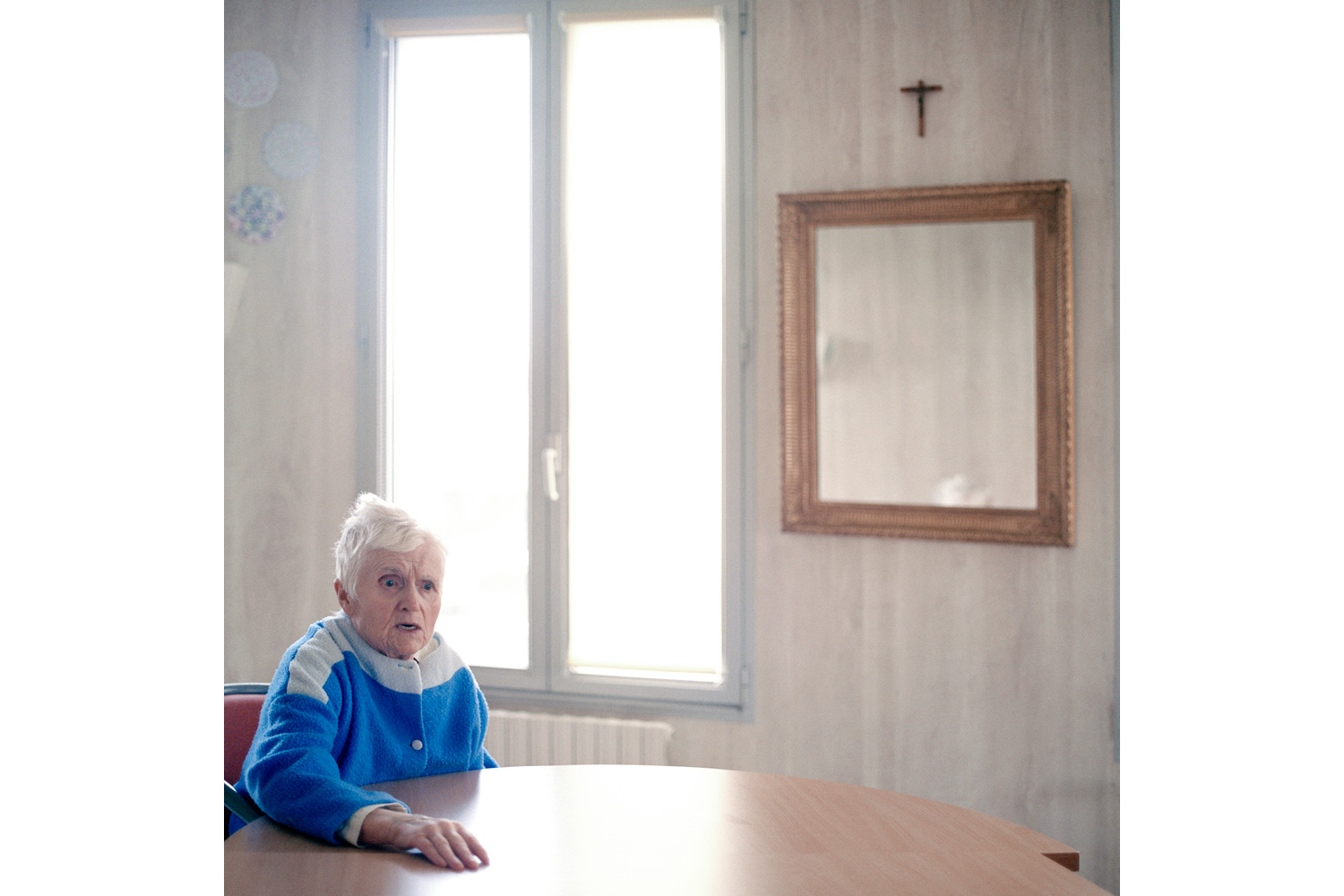 A resident sits in the ward's common room. She is talking aloud to someone the photographer cannot see. The age-related disease is a mystery as very little is known about its causes. There is no cure for Alzheimer's disease although medication has been proved to slow down the developing process of the symptoms