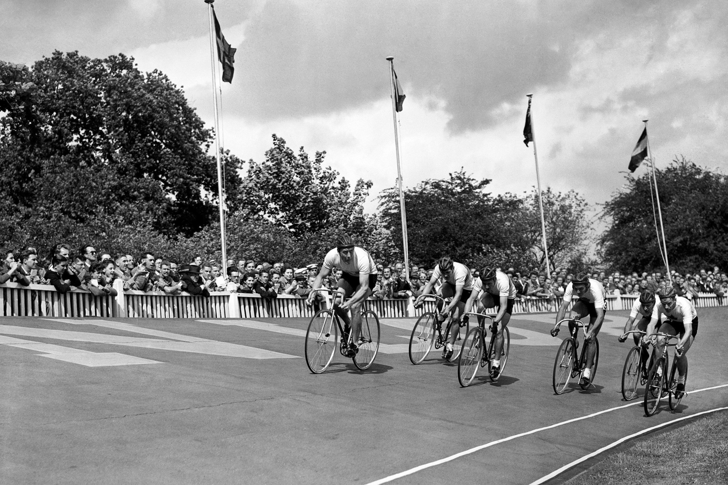 The Great Britain cycling team, including Tommy Godwin, laps Canada in the 4000-meters race at the 1948 Olympics.