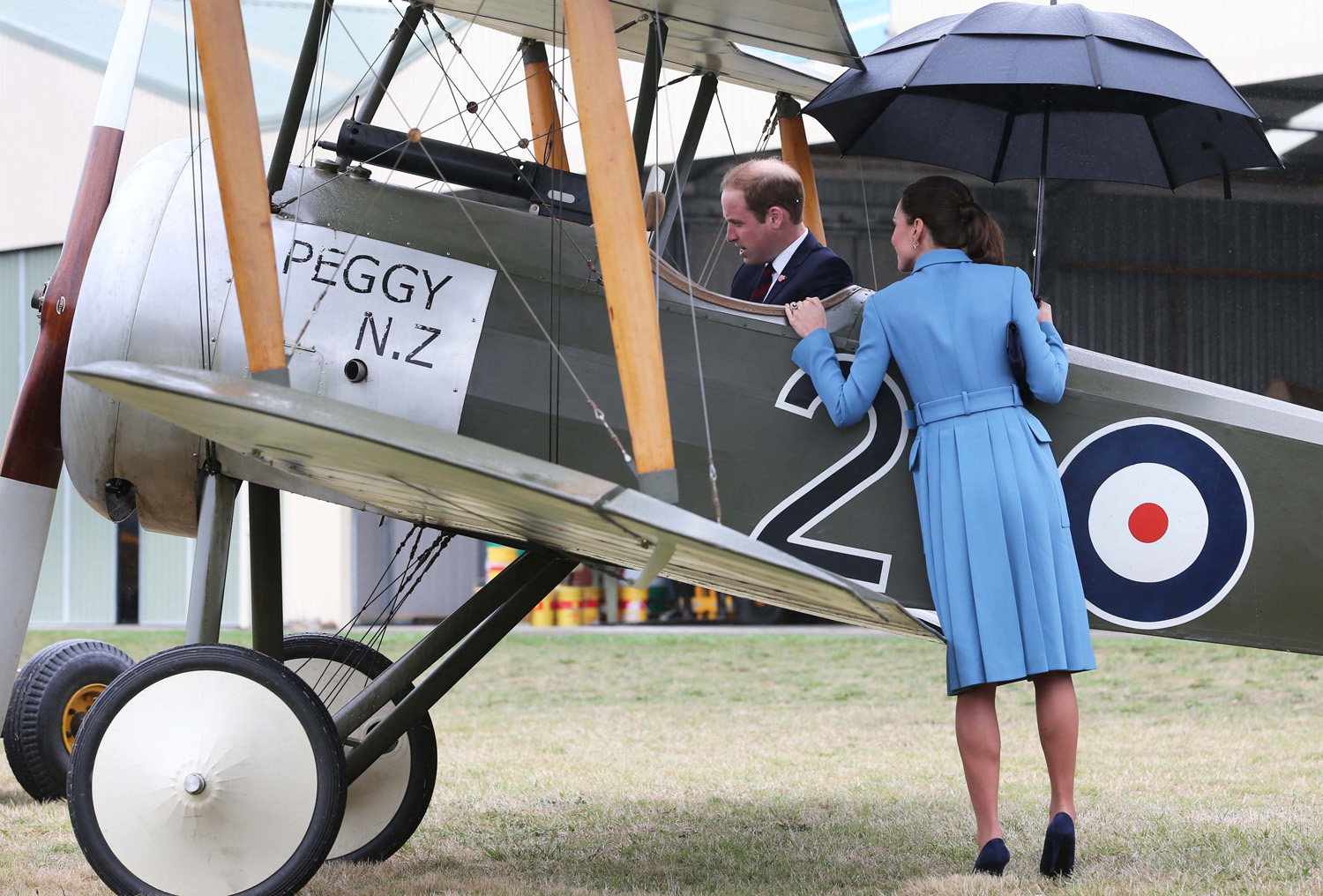 <strong>Under My Umbrella</strong>Catherine, Duchess of Cambridge watches Prince William, Duke of Cambridge sit in a plane as they attend a WW1 commemorative and Flying Day at Omaka Aviation Heritage Centre on April 10, 2014 in Blenheim, New Zealand.