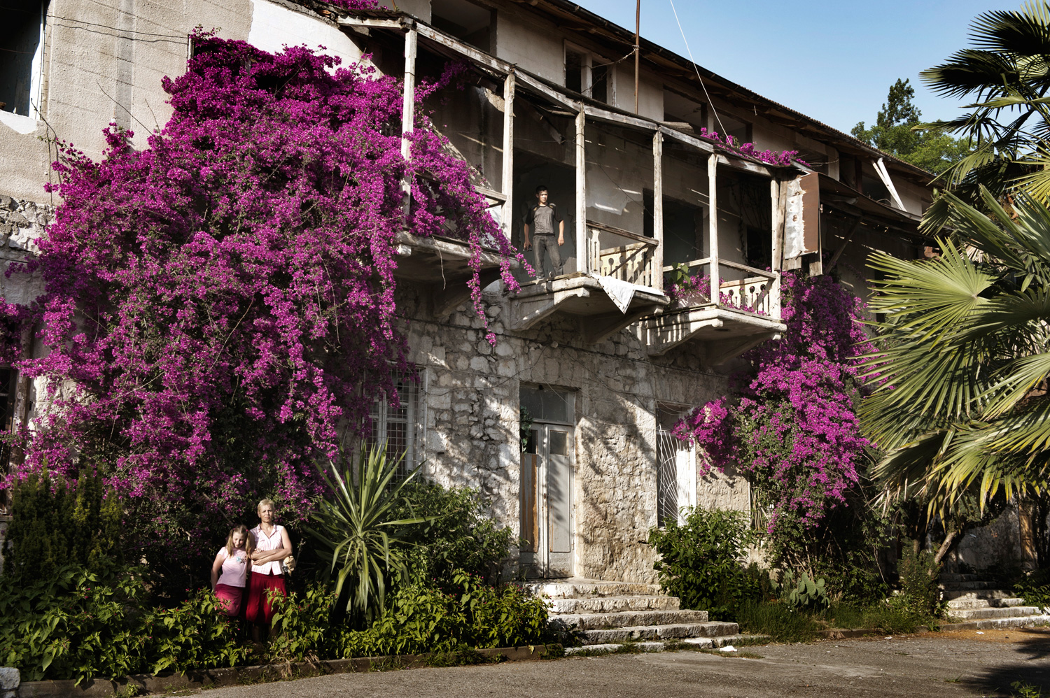 Russian tourists pose in front of an abandoned 19th-century palace of the Prince of Oldenburg in Gagra.