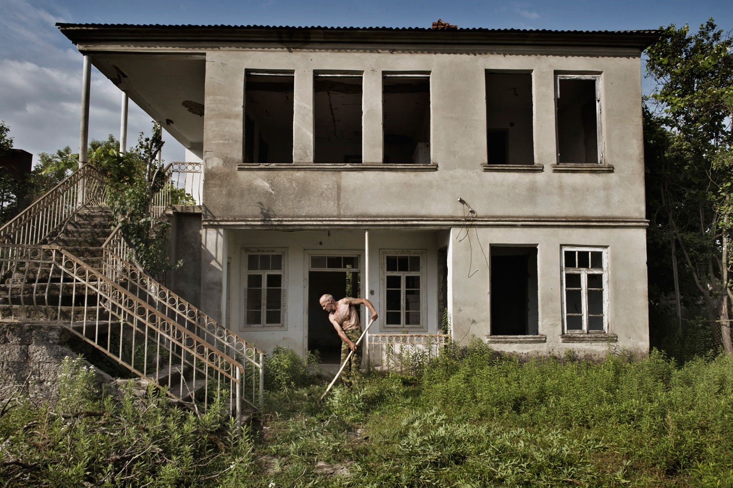 An Abkhaz man mows the lawn near an abandoned house where a Georgian family used to live.