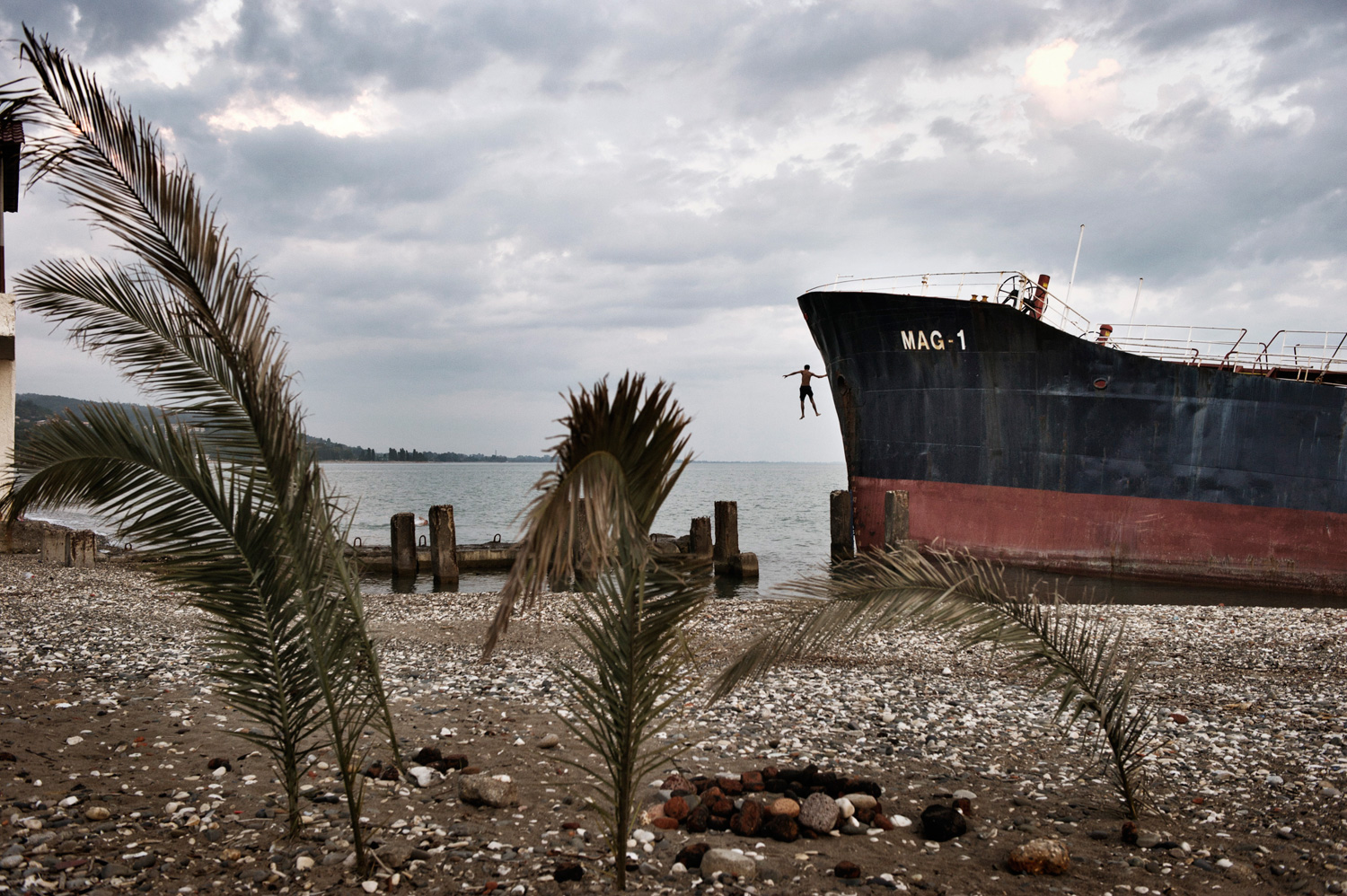 An Abkhaz boy jumps from an abandoned Turkish freighter beached near central Sukhumi, Abkhazia. After more than 15 years of economic blockades by Georgia, investment in Abkhazia is almost nonexistent–the resorts are empty, and the economy is stagnant.